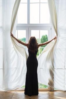 Giovane donna snella apre la finestra