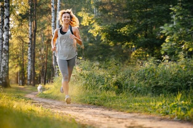 Una giovane donna snella in tuta da ginnastica corre all'alba nel parco sportiva di verde nella foresta