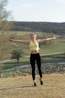 Una giovane ragazza atletica esile in abiti sportivi esegue una serie di esercizi fitness e stile di vita sano
