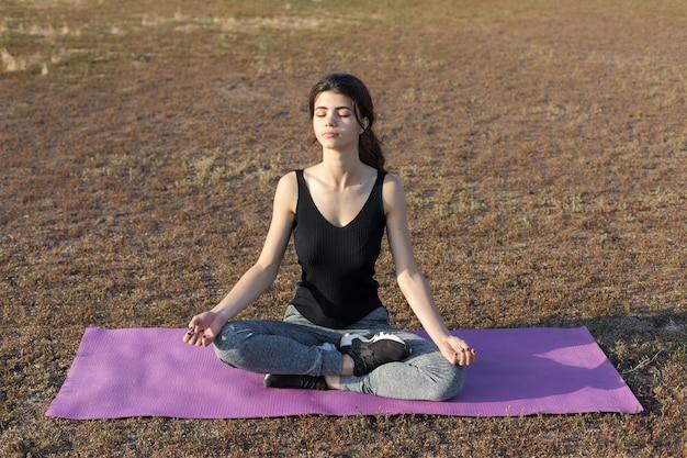 Una giovane ragazza atletica magra in abiti sportivi con stampe di pelle di serpente esegue una serie di esercizi. fitness e stile di vita sano.