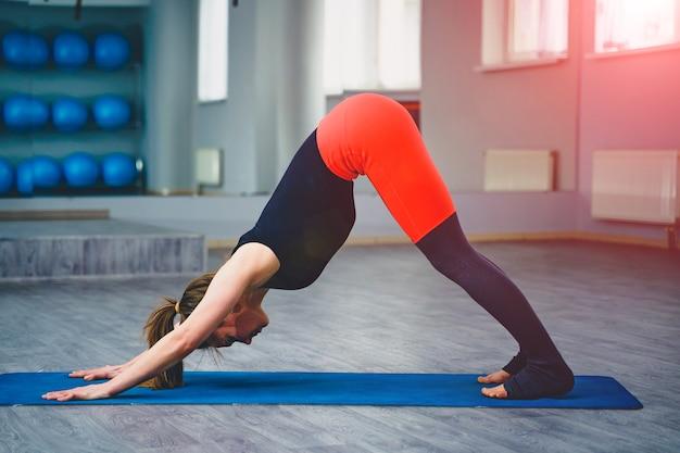 Giovane donna attraente sottile con capelli lunghi, praticare yoga al chiuso