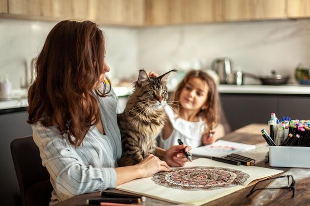 Una giovane madre snella e bellissima con una figlia carina e un gatto maine coon sta dipingendo in cucina...