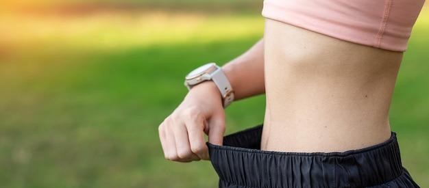 Femmina giovane corpo sottile in abiti sportivi rosa, donna in buona salute con la sua vita sottile.