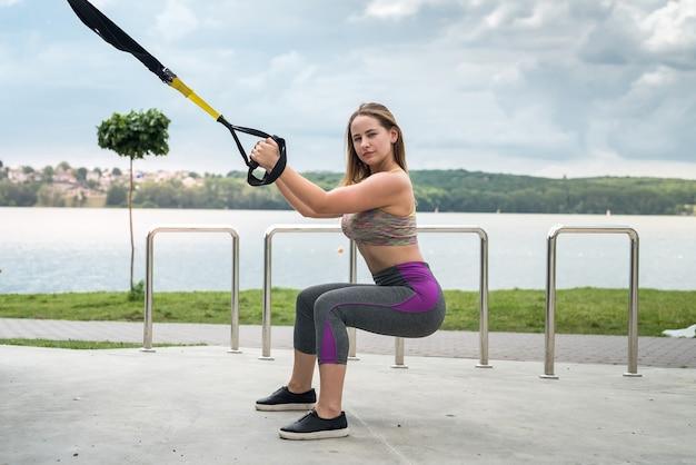 Giovane atleta femminile esile che si allena utilizzando trx in natura. uno stile di vita sano. rendi la tua macchina del corpo