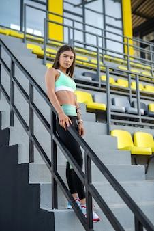 La giovane atleta femminile magra che si riposa dopo l'allenamento in abbigliamento sportivo in piedi vicino al colore si siede allo stadio
