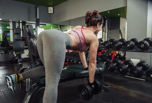 Giovane donna slim fit facendo un esercizio tirando un manubrio a una cintura in un'inclinazione con una mano appoggiata su una panchina in palestra. allenamento con i pesi gratuito