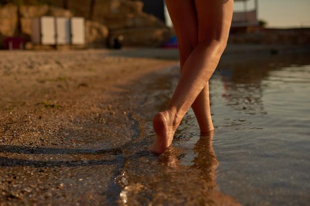 La giovane ragazza magra va a nuotare sulla spiaggia della città sullo sfondo dello spogliatoio