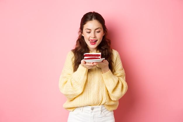 Giovane ragazza magra si lecca le labbra dalla tentazione, guardando un delizioso pezzo di torta con il desiderio di morderlo, in piedi con il dessert contro il muro rosa.