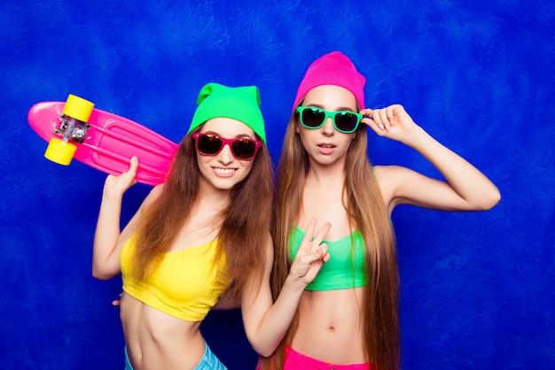 Giovani ragazze magre che tengono skateboard e gesticolano con due dita
