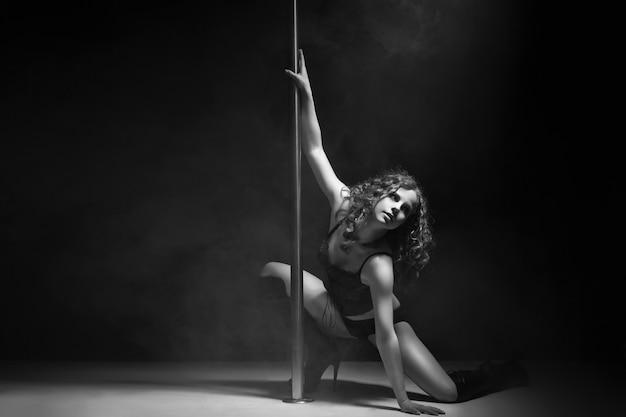 Giovane donna di danza del palo esile che si esercita su sfondo scuro