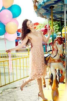 Giovane ragazza sexy alta e sottile con palloncini colorati accanto a un cavallo attarction nel parco estivo