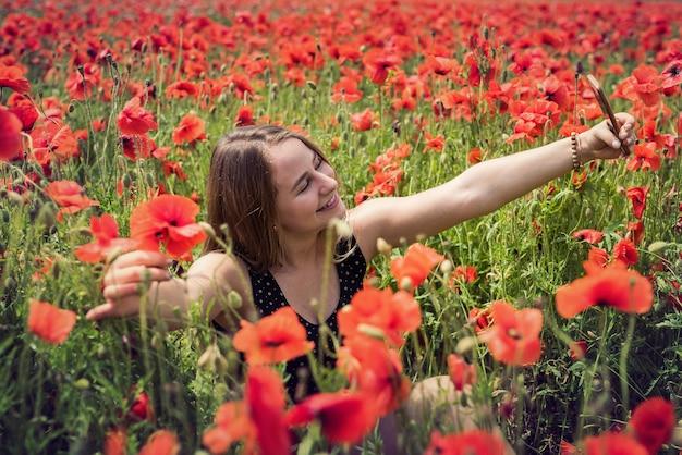 Giovane donna sottile in top corto nero in campo con papaveri in fiore, libertà alla natura