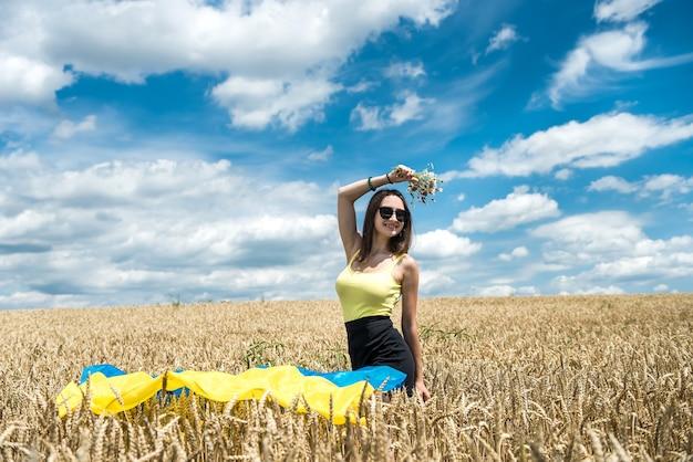 Giovane donna magra in bandiera blu-gialla dell'ucraina sul campo di grano in estate