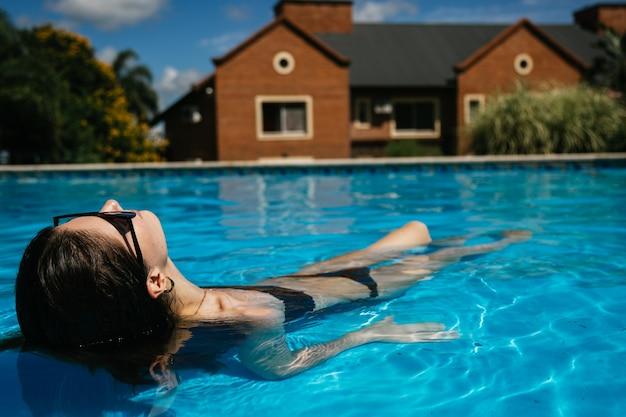 Giovane donna sottile che gode nell'acqua di una piscina dell'hotel.