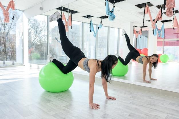 Giovane donna sottile in palestra che riposa sulla palla di pilates in forma. giovane donna che fa allenamento sulla palla fitness. uno stile di vita sano