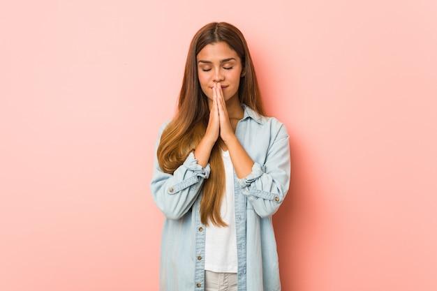 Giovane donna sottile che tiene le mani in preghiera vicino alla bocca, si sente sicura.