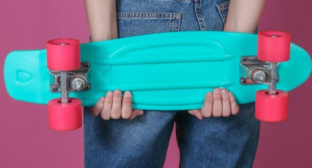 La giovane donna esile in jeans tiene il bordo di plastica dell'incrociatore nelle sue mani su fondo rosa. moda hipster giovanile. divertimento estivo. colpo dello studio. tagliare la foto