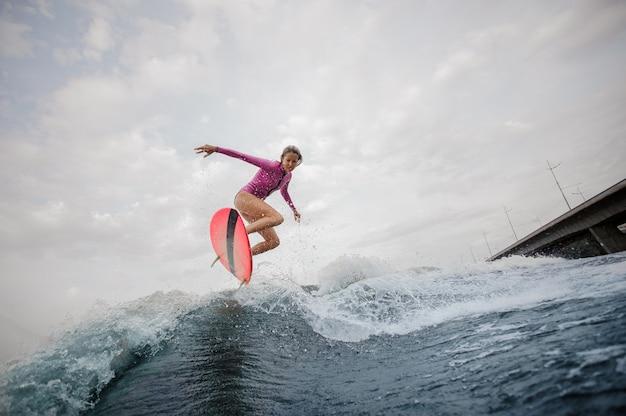 Giovane donna esile che salta sull'onda blu contro il cielo grigio