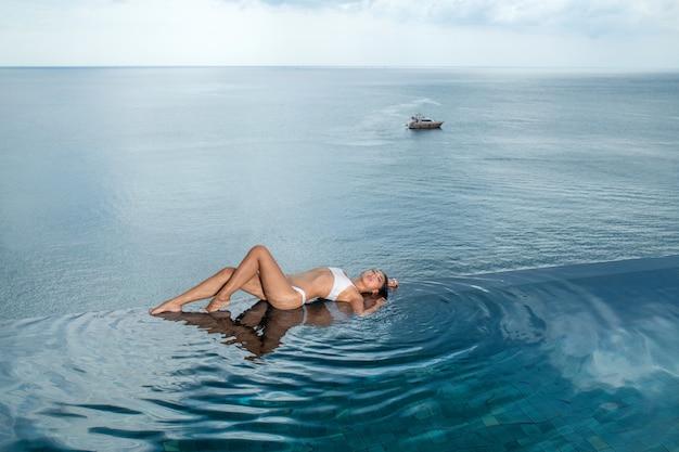 Giovane donna esile che posa sul bordo della piscina a sfioro di lusso. barca in mare.