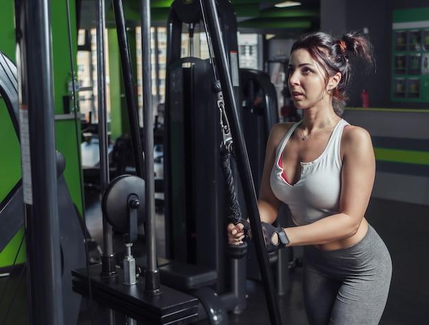 Giovane donna sottile pratica estensione delle braccia con funi in macchina ginnica in palestra