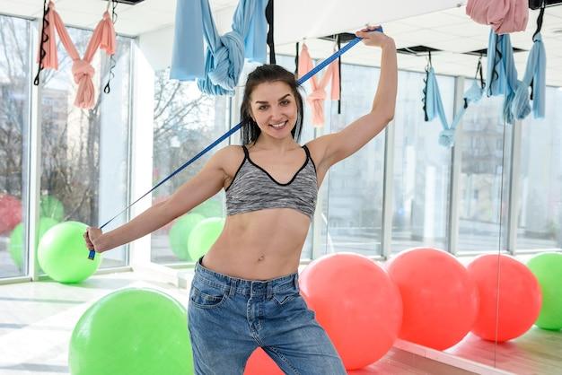 Giovane donna sottile in alto misurando il petto in palestra. concetto di stile di vita sano