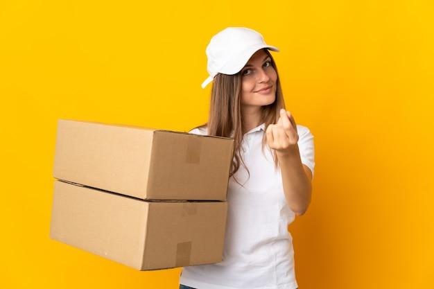 Giovane donna di consegna slovacca isolata su fondo giallo che fa i soldi gesture