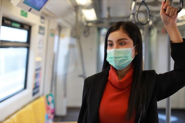Giovane donna asiatica intelligente di affari che indossa la protezione della maschera per prevenire l'infezione da virus covid19 da persone in treno o cattivo inquinamento atmosferico pm2,5 crepuscolo