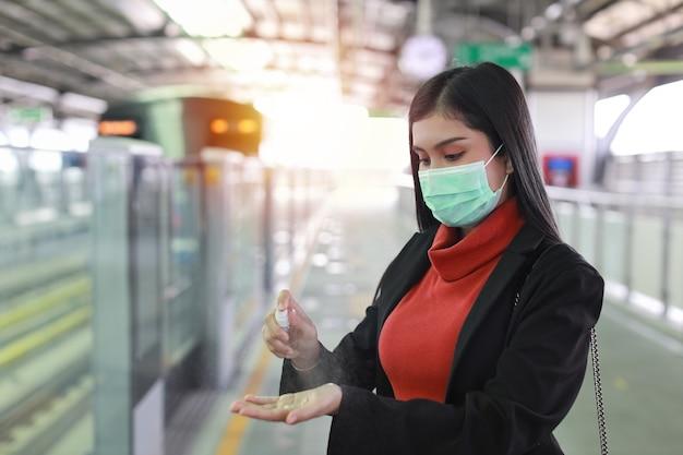 Giovane donna asiatica intelligente di affari che indossa la protezione della maschera per prevenire l'infezione da virus covid19 da persone in treno, utilizzando disinfettante per le mani a spruzzo di alcol