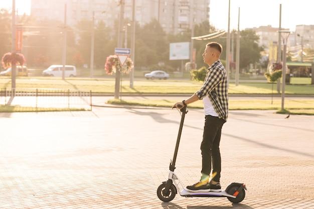Giovane uomo intelligente hipster in sella a uno scooter elettrico moderno e veloce vicino a un'enorme costruzione contemporanea in un paesaggio aperto su una strada di campagna. trasporto ecologico. trasporto elettrico ad alta velocità