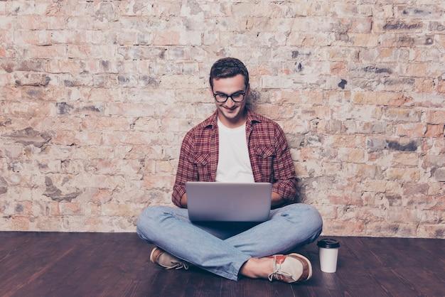 Giovane uomo intelligente con una tazza di caffè che digita sul computer portatile