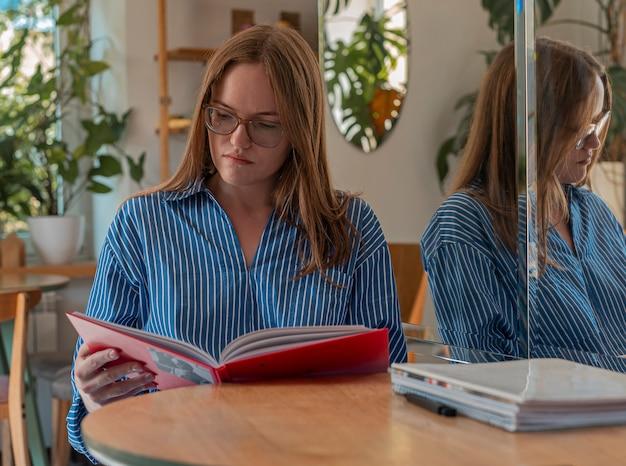 Giovane donna astuta in occhiali che legge libro nel lettore moderno della caffetteria in cafe