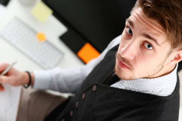 Giovane uomo di sorriso al ritratto del primo piano dell'area di lavoro dell'ufficio. collare bianco assegno carte monetarie mercato azionario entrate interne ispettore lista guadagni concept