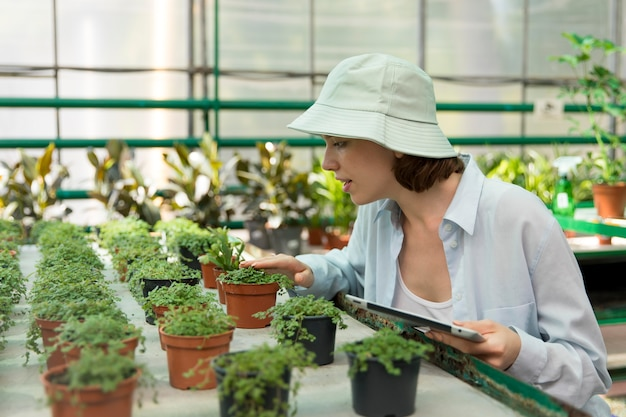 Giovane donna sorridente che lavora in una serra