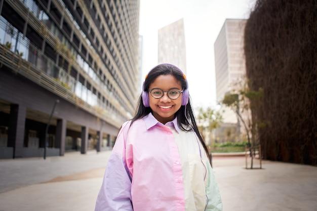 Giovane afroamericano sorridente che guarda l'obbiettivo vestito colorato ascoltando musica con le cuffie...