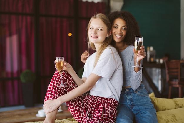 Giovane donna afroamericana sorridente con capelli ricci scuri e bella donna con capelli biondi che si appoggiano a vicenda con bicchieri di champagne in mano mentre felicemente insieme