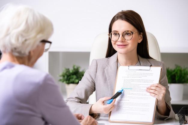 Giovane agente sorridente o imprenditrice con evidenziatore blu che punta alla carta di assicurazione mentre lo mostra alla donna in pensione