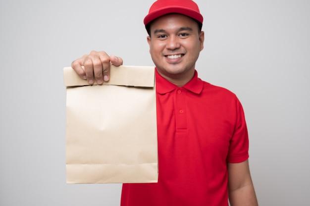 Giovane uomo asiatico sorridente di consegna in uniforme rossa che tiene la consegna del cibo del sacchetto di carta