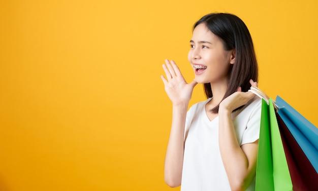 Giovane donna asiatica sorridente che tiene multi sacchetti della spesa colorati e che annuncia con le mani alla bocca su giallo chiaro.