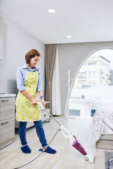 Giovane donna asiatica sorridente aspirapolvere pavimento nel suo appartamento