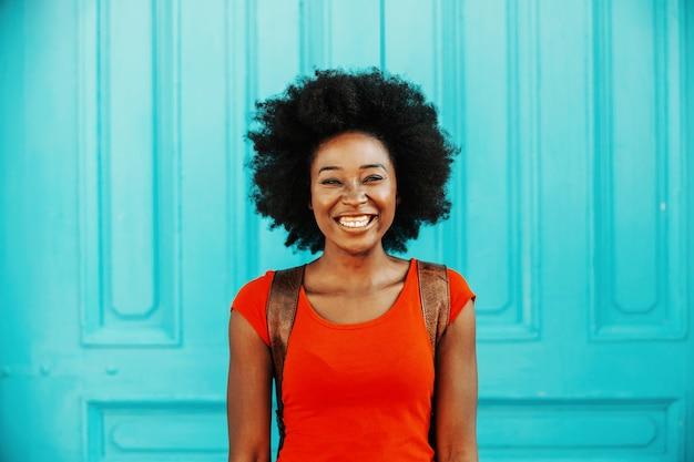 Giovane donna africana attraente sorridente con capelli ricci corti in piedi all'aperto