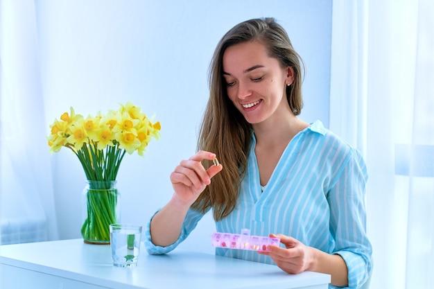 Giovane donna felice attraente sorridente che prende integratore alimentare vitamina omega 3 per il supporto della salute delle donne. softgel di olio di pesce, vitamina d e c per l'immunità e la prevenzione delle malattie