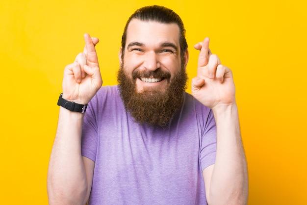Giovane uomo barbuto sorridente che incrocia le dita per buona fortuna, esprimendo un desiderio