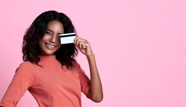 Bella donna africana sorridente dei giovani che mostra la carta di credito a disposizione sopra il fondo rosa dell'insegna