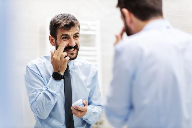 Giovane imprenditore barbuto bello sorridente in piedi davanti allo specchio in bagno e mettere la crema sul viso