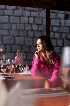 Una giovane e bella ragazza sorridente gode delle splendide viste sul mare. seduto in un bar e guardando le splendide viste.