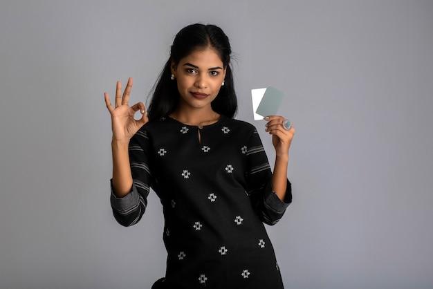 Giovane bella donna o ragazza sorridente che presenta la carta di credito in mano che mostra fiducia e sicurezza per effettuare il pagamento.