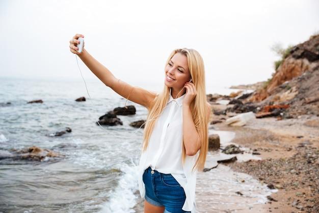 Giovane bella donna sorridente che ascolta musica e che fa selfie mentre levandosi in piedi sulla spiaggia rocciosa