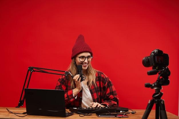 Giovane blogger sorridente seduto al tavolo con laptop e tastiera musicale e cantando sulla fotocamera