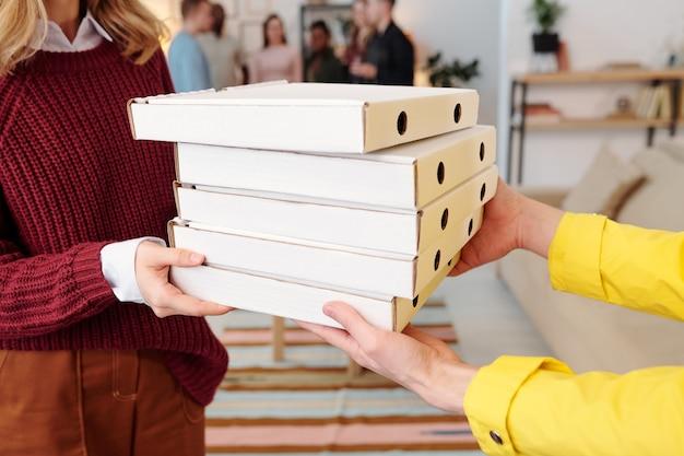 Giovane donna bionda sorridente in abbigliamento casual intelligente che prende una pila di scatole di cartone quadrate imballate con pizza dalle mani del corriere maschio in uniforme
