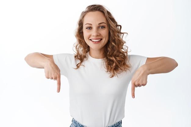 Giovane donna bionda sorridente che punta verso il basso con un viso allegro e fiducioso, che mostra testo promozionale sullo spazio della copia, muro bianco